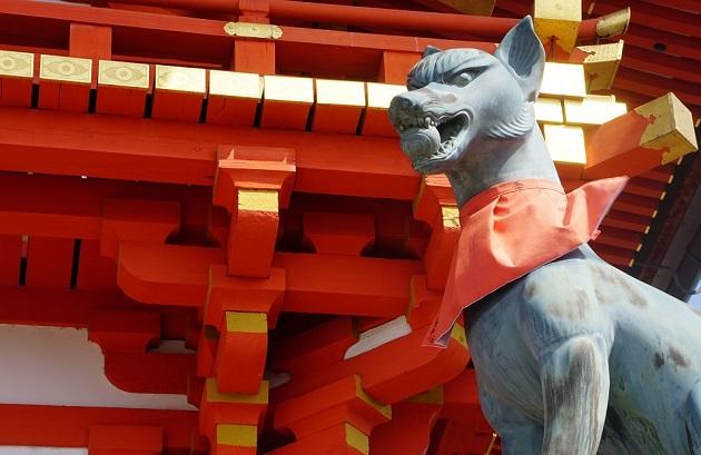 朱が眩しい伏見稲荷大社の社殿と白狐の像。