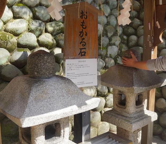 定番の人気スポット「おもかる石」。霊石をあげて運試しに挑戦して頂きたい。