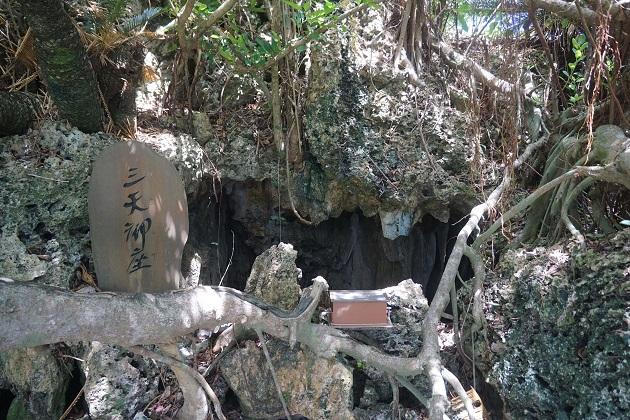 天、地、海の神が集うパワースポット。小さな鍾乳洞にガジュマルの木が絡みついている。