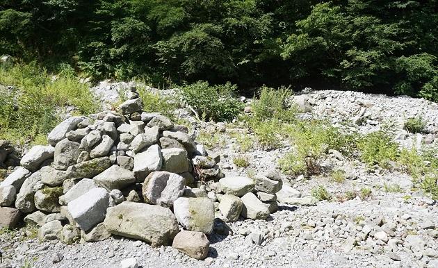 積み石が点在する賽の河原。プリミティブな祈りのカタチに触れることができる。