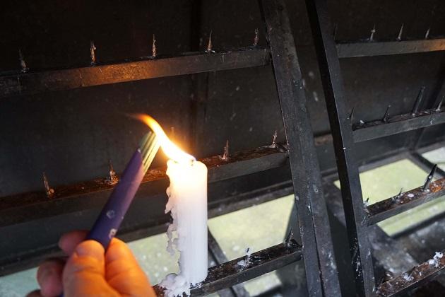 銭洗弁財天宇賀福神社の正しい参拝方法は社務所でろうそく、線香、ざるを受け取ることに始まる。ひときわ太いろうそくに種火がともされている。