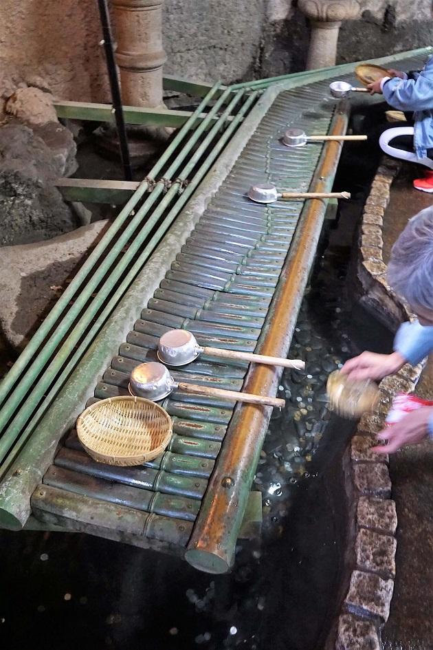 奥宮では弁財天を祭るお社を参拝した後にお金を清める洗い場に向かう。洗い場には柄杓とざるを置くための長椅子のようなスペースがある。