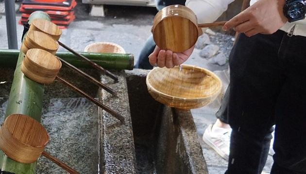 御金神社の手水舎。お金を清めるためのざるが置いてある。
