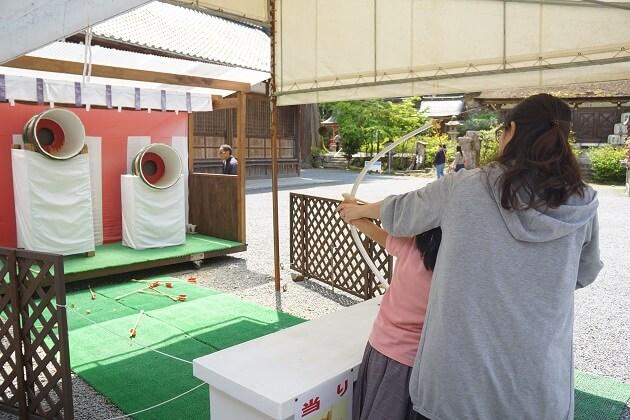松尾大社の樽占い。弓矢で樽の的を狙う。