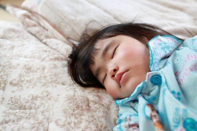 ふかふかの布団に寝る女の子のイメージ写真。