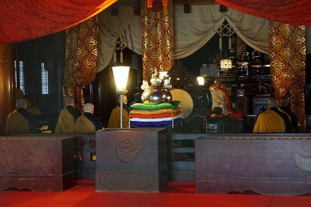 豊川稲荷の本殿で読経する僧侶ら